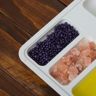 ハーバルロックソルト。木製の机の上の白い皿に油とブルーベリー化粧品