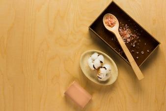 Herbal soap, raw cotton flower and hawaiian sea salt on wooden table
