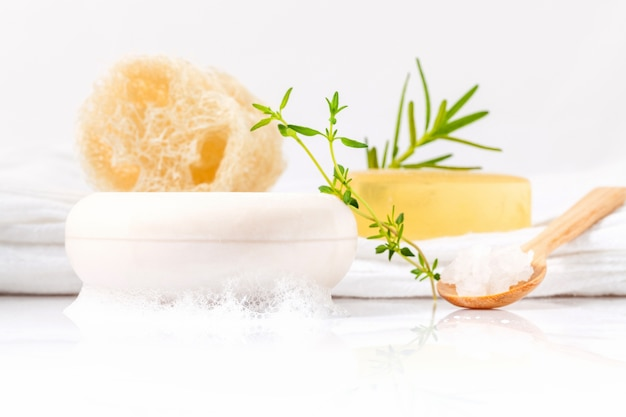 Herbal spa soap bar with herbs and luffa isolated on white background.