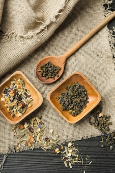 Herbal spices on wooden bowl and spoon over sack