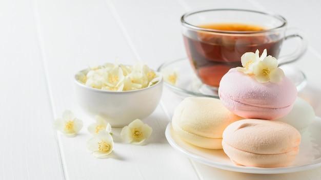Травяной чай, миска с маршмеллоу и цветами жасмина на деревенском столе. состав утреннего завтрака.