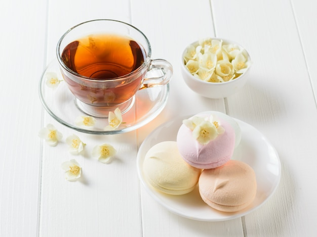Травяной чай, миска с маршмеллоу и цветами жасмина на столе. состав утреннего завтрака.