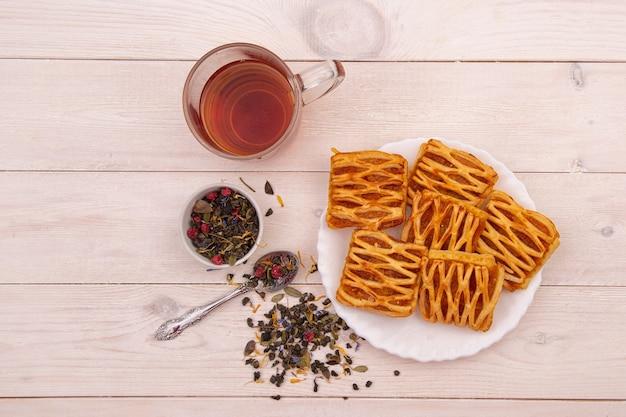 木製のテーブルにジャムとハーブティーとクッキー。朝食、自家製ケーキ、甘さのコンセプト。