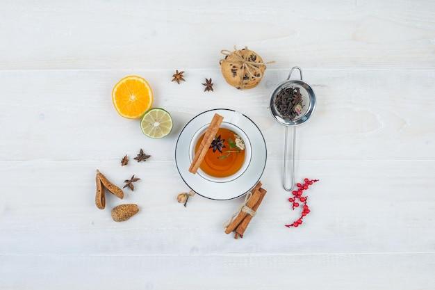 ハーブティーと茶漉し、ハーブ、柑橘系の果物とクッキー