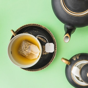Herbal tea bag in the cup with teapot and sugar cubes on green background
