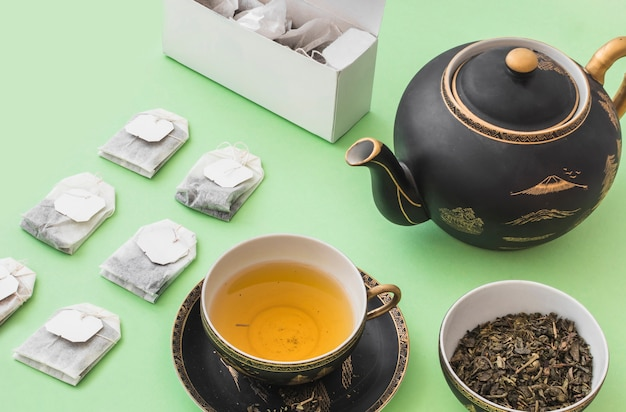 Herbal tea bags and tea cup on pale green paper background