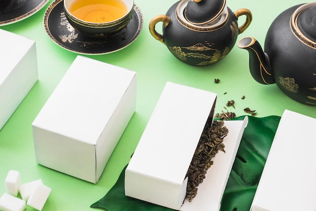 Herbal tea boxes with tea and sugar cubes on green backdrop