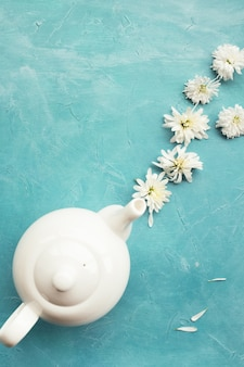 Herbal tea and chrysanthemums on a blue wall. healthcare lifestyle. pure and tenderness.