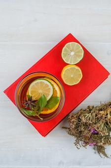 Herbal tea and citrus fruits on a red placemat with a flower bouquet