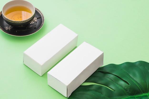 Травяной чашки чая и две белые коробки с листьями на зеленом фоне