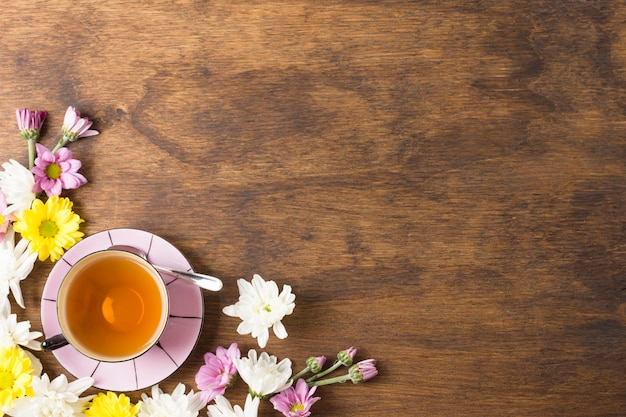 Herbal tea cup and beautiful blossoms on the corner of the wooden background