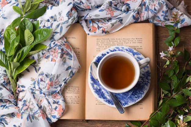 Herbal tea cup and saucer on an open book with leaves and scarf on table