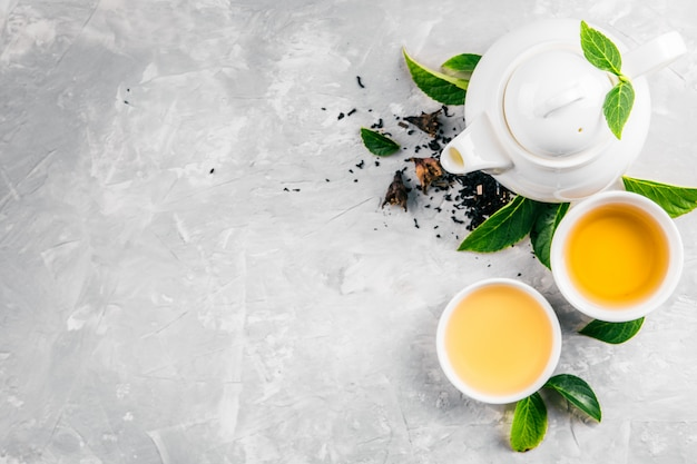 Herbal tea, cups and teapot with leaves on grey concrete background.