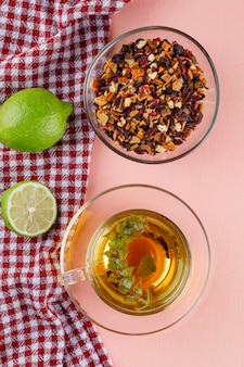 Herbal tea in a glass cup with limes, dried herbs flat lay on pink and kitchen towel