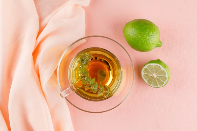 Herbal tea in a glass cup with limes flat lay on pink and textile