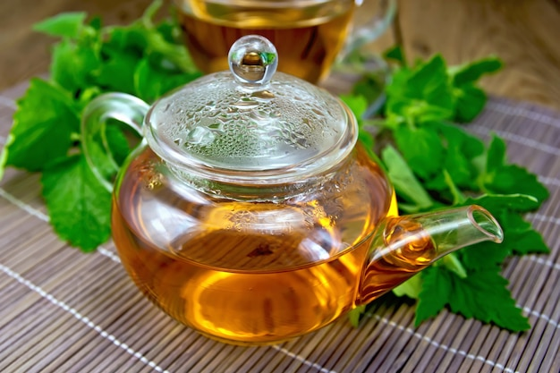 Herbal tea in a glass teapot of fresh mint leaves on bamboo napkin background and wooden board