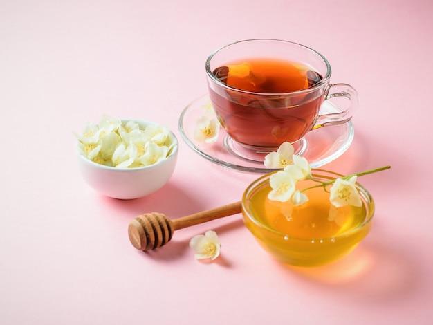 Травяной чай, мед, цветы жасмина и деревянной ложкой на розовом столе. состав утреннего завтрака.