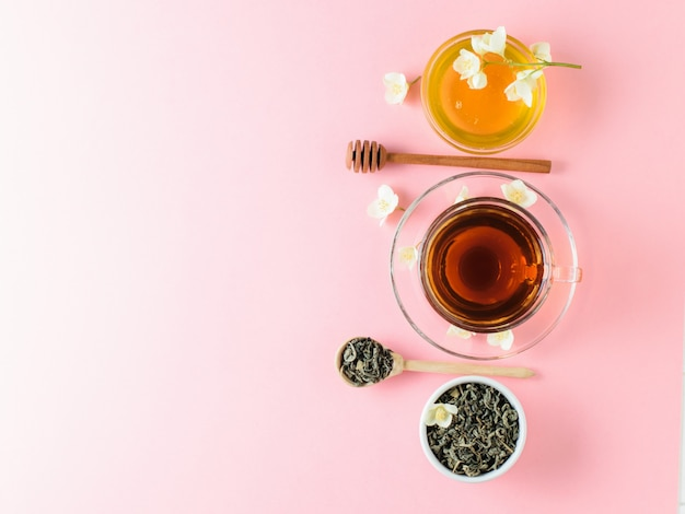 Herbal tea, honey, jasmine flowers and a wooden spoon on a pink table. the composition of the morning breakfast. flat lay.