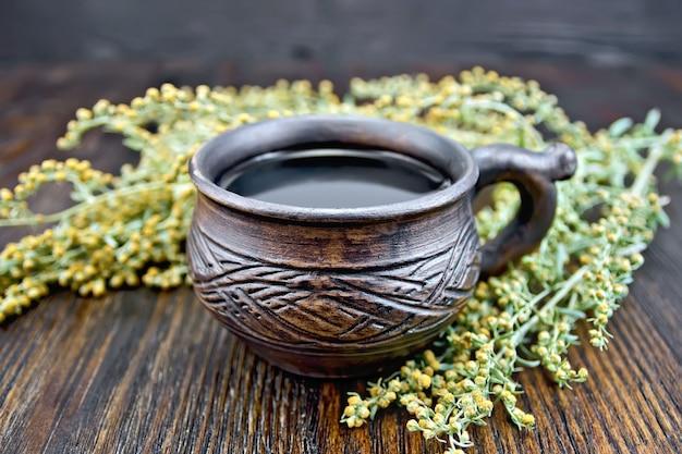 점토 컵에 허브 차, 나뭇 가지 회색 쑥, 나무 판의 배경에 종이에 말린 쑥