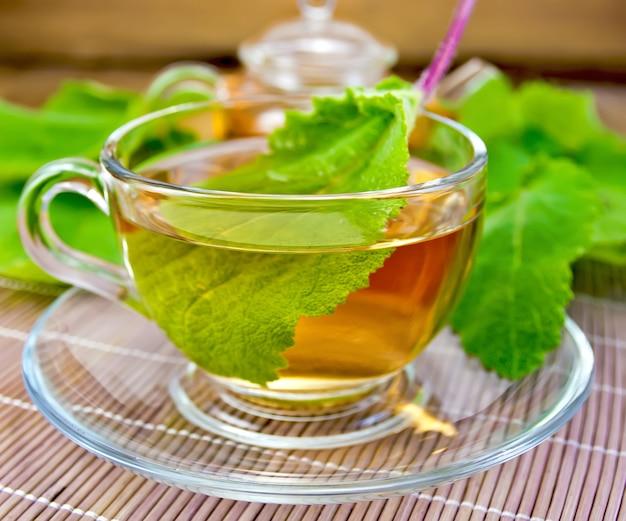 ガラスのカップとソーサーのハーブティーと背景の竹ナプキンと木の板にセージの葉のティーポット
