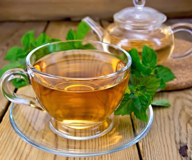 Травяной чай в стеклянной чашке и чайнике, свежие листья мяты на фоне деревянных досок