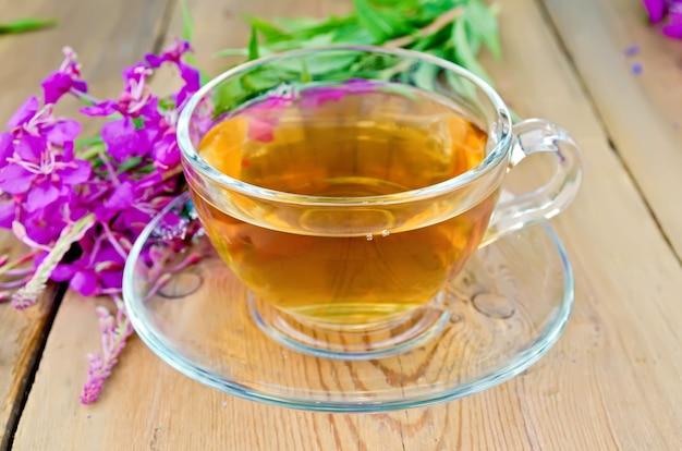 Травяной чай в стеклянной чашке, кипреи свежие цветы на фоне деревянных досок