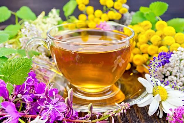 ガラスカップのハーブティー、生花ファイアウィード、タンジー、カモミール、クローバー、ノコギリソウ、メドウスイート、木の板の背景にミントの葉