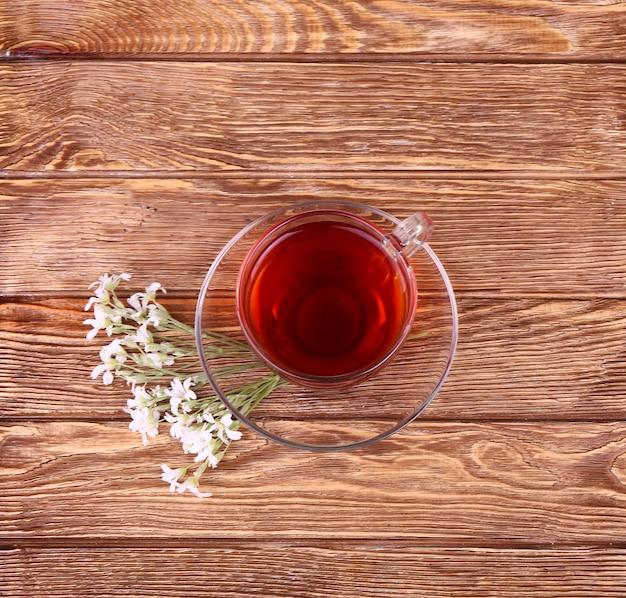 ガラスカップのハーブティー、木の板の背景に生花