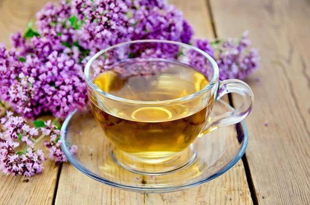 유리 컵에 허브 차, 나무 판의 배경에 신선한 오레가노 꽃