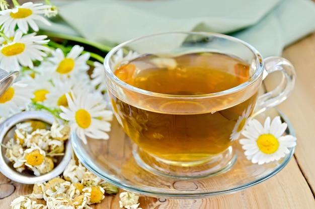 유리 컵에 허브 차, 마른 카모마일 꽃이 달린 금속 체, 신선한 꽃, 데이지, 나무 판의 배경에 녹색 천