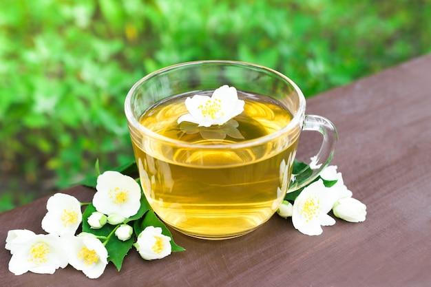 Травяной чай в стеклянной чашке с белыми цветами жасмина на зеленом естественном фоне