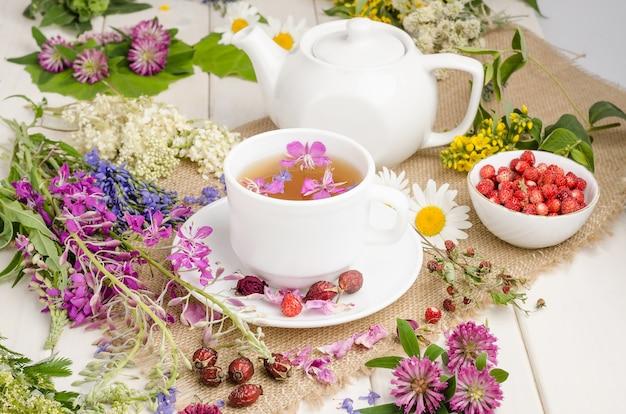 花と白いカップのハーブティー。茶道。カモミール入りのお茶、ワイルドローズとクローバー入り