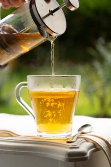 Травяной чай в стеклянной чашке, подается в саду. завтрак в саду летом
