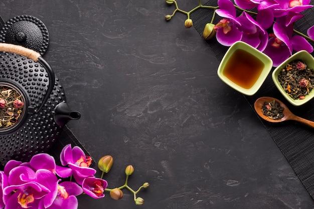 Herbal tea ingredient and pink fresh orchid flowers twig on black surface