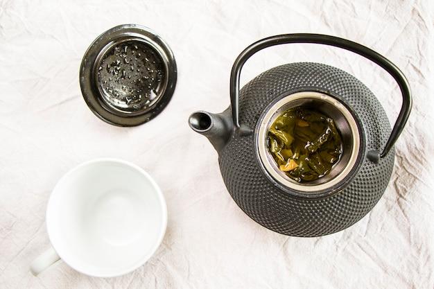 Herbal tea, iron teapot and cup of tea