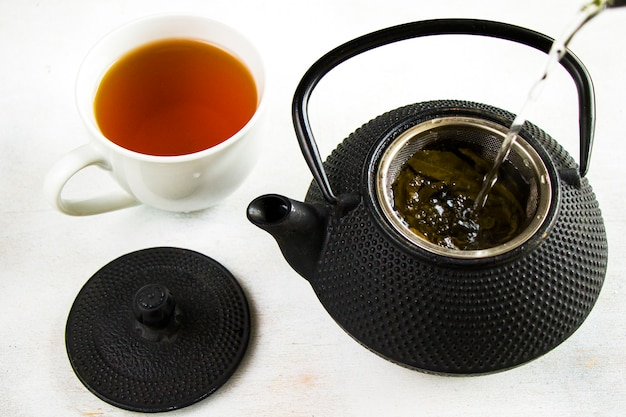 Herbal tea, iron teapot and cup of tea