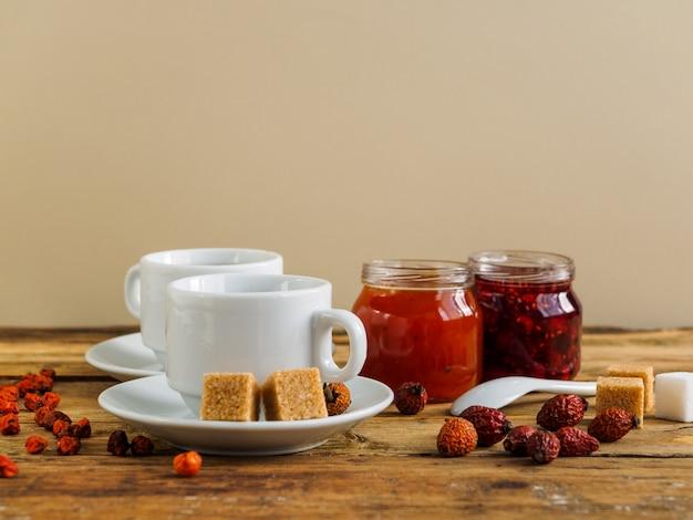 Травяной чай, джем и сухофрукты на желтом фоне. скопируйте пространство.