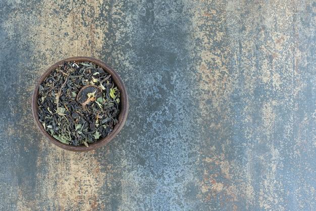 Листья травяного чая в деревянной миске.