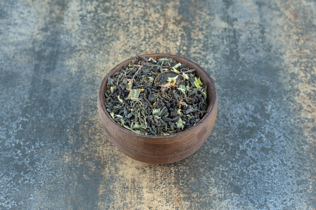 Herbal tea leaves in wooden bowl.