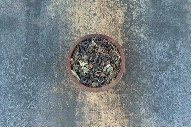 Foglie di tisana in ciotola di legno.