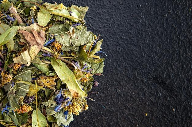 ハーブティーの薬草は花を残し、テーブルに新鮮な食事を残しますコピースペースフード