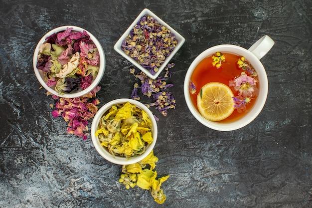 Herbal tea near bowls of dry flowers on grey