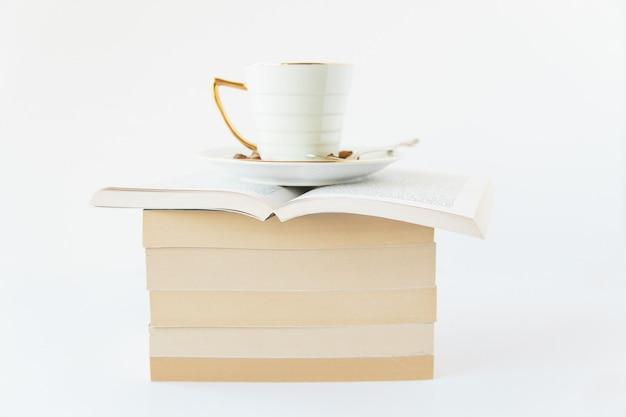 白い背景の上の閉じた本のスタックの上に開いた本の上に白いカップのハーブティー