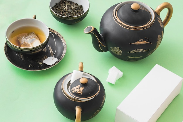 Herbal tea set with white box on green paper background
