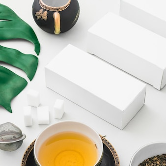 Herbal tea, sugar cubes, tea strainer and white boxes on backdrop