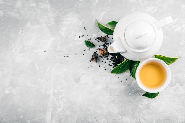 Herbal tea and a teapot on a concrete background