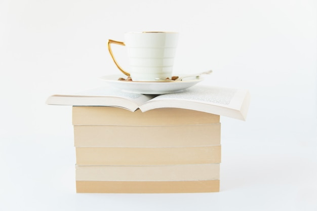 Herbal tea on a white cup over an opened book over a stack of closed books on white background