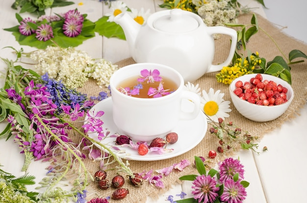 Herbal tea in a white cup with flowers. tea ceremony. tea with chamomile, with wild rose and clover