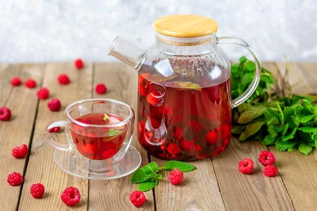 ガラスのティーポットと木製のテーブルの上のカップにベリー、ラズベリー、ミントの葉、ハイビスカスの花とハーブティー