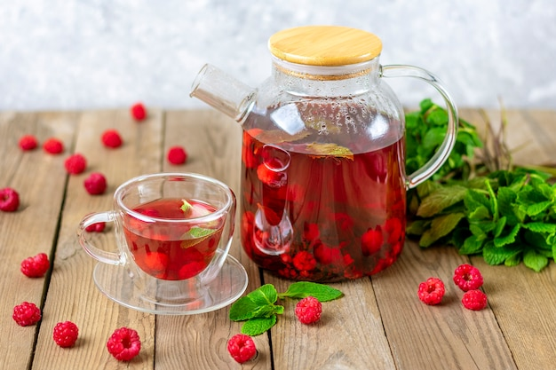 Herbal tea with berries, raspberries, mint leaves and hibiscus flowers in glass teapot and cup on wooden table